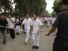 A policeman stands by a cordon tape as workers walk out of a Honda Motor factory on strike in Zhongshan, Guangdong, China, on 11 June, 2010.