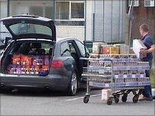 A shopper loads his car with alcohol