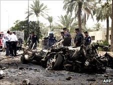 Police inspect one of the vehicles which exploded in Baghdad (20 June 2010)