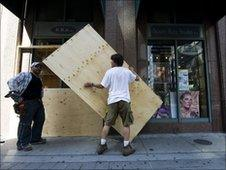 Workers install plywood sheets on street level condos in Toronto, Canada, on 23 June, 2010
