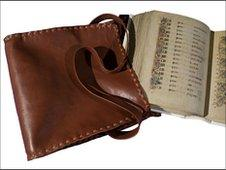 brown leather book satchel and facsimile of the Book of Kells