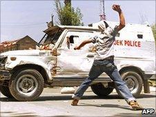 Kashmiri protester attacks a police jeep