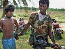 Indian security officer detains an alleged Maoist in West Bengal