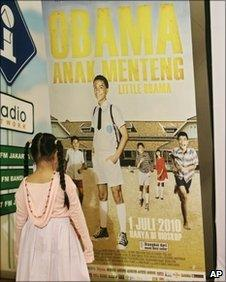 A girl looks at a poster for the film Obama Anak Menteng before its premiere in Jakarta