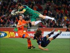 Iker Casillas of Spain catches the ball ahead of Robin Van Persie of the Netherlands as Carles Puyol of Spain falls to the ground during the World Cup final