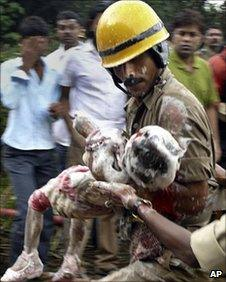 rescue worker carrying a child who survived the crash
