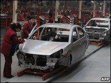 Chinese workers assemble cars at an auto plant in Hefei, central China's Anhui province