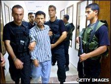 An alleged collaborator is arrested by Hamas police in Gaza