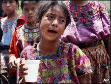 A child reacts as villagers recover bodies of two victims of storm in western Guatemala on 31 May 2010