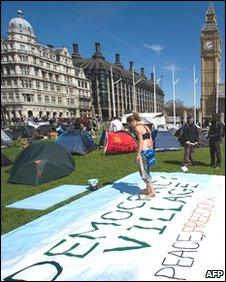 """A woman paints a banner in the """"Democracy Village"""" in Parliament Square"""