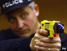 Policeman demonstrates using a Taser stun gun