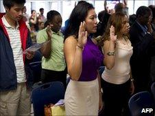 People take the oath of allegiance at a naturalization ceremony in New York