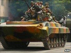 Kyrgyz soldiers drive an armoured vehicle in Osh, 11 June