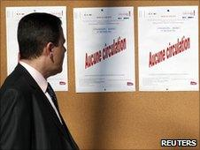 """A passenger reads a notice that reads """"no traffic"""" during a national strike at Strasbourg's railway station"""