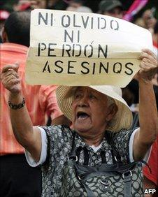 A supporter of Manuel Zelaya holds a banner reading Killers will not be forgetting or forgiven