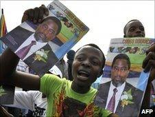 A man carries pictures of Congolese president Joseph Kabila during independence day celebrations