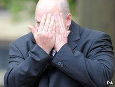 Paul Barrett hides his face as he leaves court