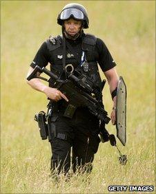 Armed police officer searches countryside