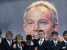 Nine children named after Tony Blair appear in front of a poster of the former prime minister in Kosovo