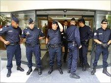 Police officers stand outside the offices of Patrice de Maistre, Friday, July 9, 2010