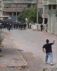 Police run towards a man in Baniyas, Syria, 27 May 2011