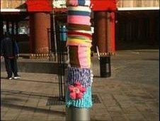 Seven short multi-coloured scarves on a lamppost