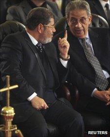 Mohammed Mursi and Amr Moussa talk together at St Mark's Cathedral in Cairo on 6 January