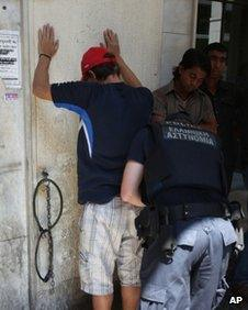 Police check suspected illegal migrants in central Athens, Sunday, Aug. 5, 2012.