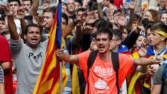 Students raise their arms during a demonstration marking the first anniversary of Catalonia's independence referendum.