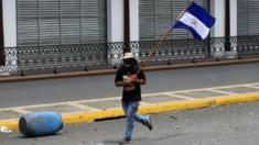 A demonstrator holds a national flag during clashes with riot police in a protest against Nicaragua's President Daniel Ortega's government in Masaya, Nicaragua June 2, 2018.