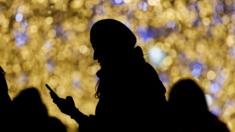 a woman holds a phone near christmas and new year light installation in moscow russia