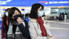 People arrive at Heathrow Airport wearing face masks