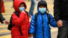 Two children wearing face masks and holding hands