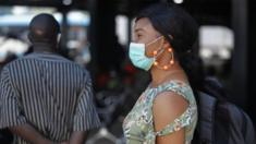 A woman wearing a surgical mask waits for a bus in Lagos, Nigeria