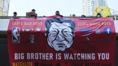 A protest banner with a picture of Xi Jinping and the slogan 'big brother is watching you;'
