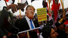Supporters of Iraqi Shia cleric Moqtada al-Sadr carry placards depicting Donald Trump