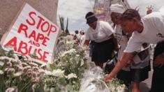 Women place white flowers outside parliament during a demonstration in Cape Town 25 November 1999, the International Day for the Prevention of Violence against Women. South Africa has a high incidence of rape with more than 50 000 reported rapes per year.