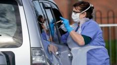 A nurse swabs a person in a car to check if they have coronavirus