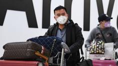 People wearing face masks arrive at London's Heathrow Airport