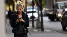 A woman uses her smartphone as she walks in New York, 13 November 2014