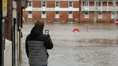 A person looking at their phone in front of flood waters