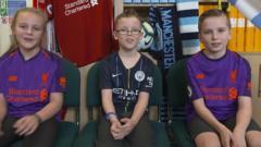 Three football fans in their team kits
