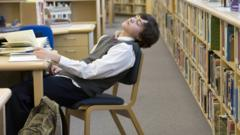 Teenager asleep at desk in school library