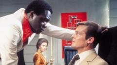 Yaphet Kotto as Dr Kananga giving Roger Moore's James Bond a grilling in Live and Let Die