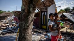 A woman with her son stands near the ruins of their home following an earthquake in Pemenang on 8 August 2018 in Lombok Island, Indonesia