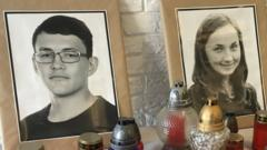 A table, covered in white linen, supports more than a dozen red candles alongside the two photos of Jan Kuciak and his fiancee Martina Kusnirova