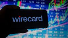 Wirecard logo on phone against stock market charts.