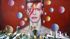 Flowers are laid in front of a mural of David Bowie