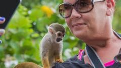 man taking selfie with monkey on shoulder