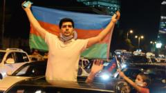 An Azeri protester holds the national flag in Baku amid pro-war demonstrations, after deadly border clashes with Armenia